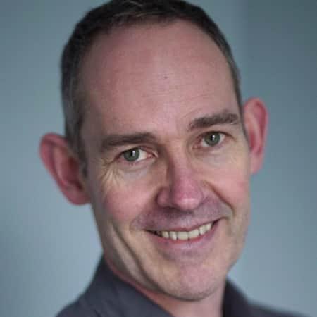 Portrait photograph of Patrick McGrady against a blue background.