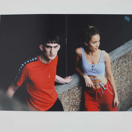 Two people modelling beside a concrete wall. One is wearing a red t-shirt and looking at the camera, the other has red trousers and a stripy crop-top on.