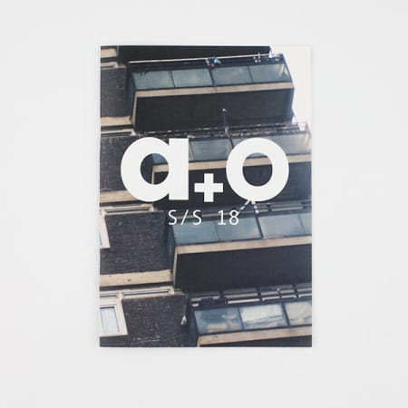 Fashion branding project by Kate Hutchens showing the outside view of a concrete tower block with the letters A + O written across in white text.
