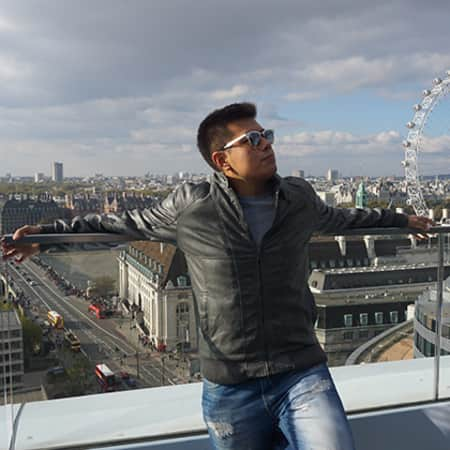 Photo of Michael Taco standing on a balcony, with a backdrop of the city of London.