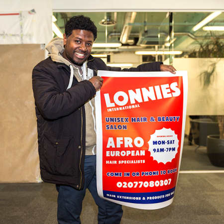 Manager Henock unpacking the designs, a poster and a signage, on behalf of Lonnies International hairdressing owner, Betty Adave-Asafu.
