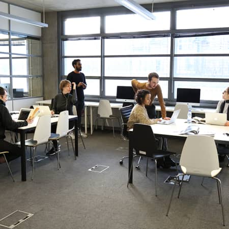 A group of postgraduate students sitting at tables, with laptops, within the Graduate School space at London College of Communication.