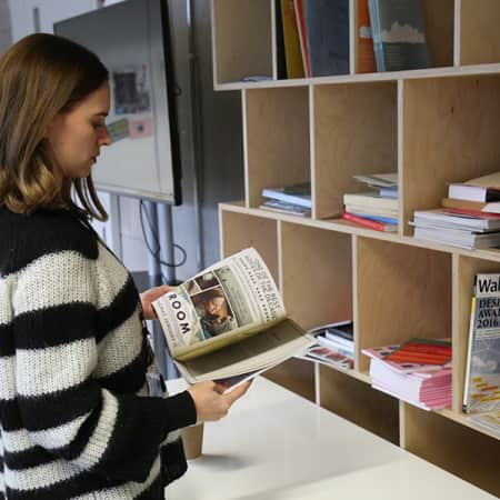 Postgraduate student reading magazine in the Graduate School Space at London College of Communication.