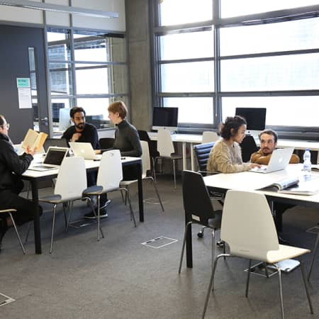 A number of postgraduate students, sitting at tables on laptops within the Graduate School space at London College of Communication.