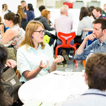 Mentors and mentees having a conversation around tables as part of the Industry Mentoring Scheme at London College of Communication.
