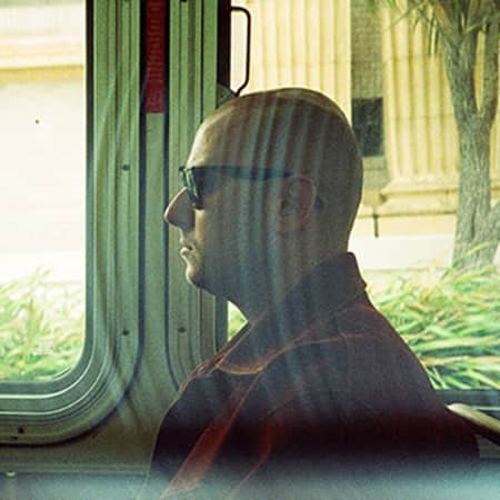 Photograph by Pascal Mowla showing the profile of a man, wearing sunglasses and sitting on a bus. Behind his head are two windows which look out onto a building, waving grass and palm trees waving in the wind.