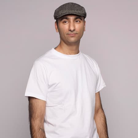 Staff profile image of Kuldeep Nazran, wearing a white t-shirt and flat cap, standing against a purple background
