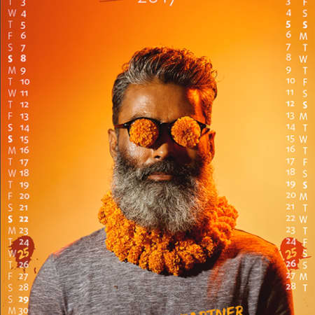 Poster of man in traditional Indian dress, with orange backdrop.