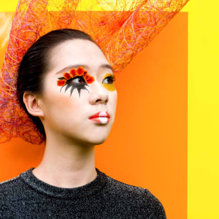 Model with orange make-up and orange and yellow backdrop.