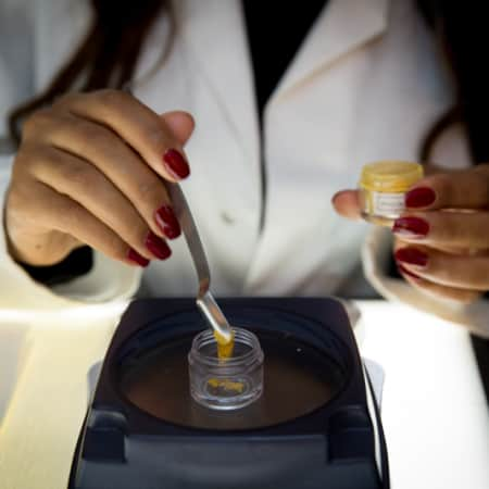 Cosmetic science student measures pigment for a lip gloss demonstration