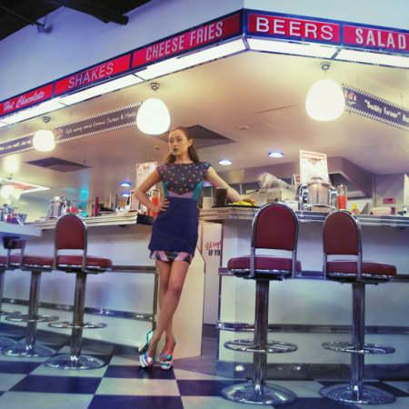 Female model sitting on a diner stall at a counter wearing apron.