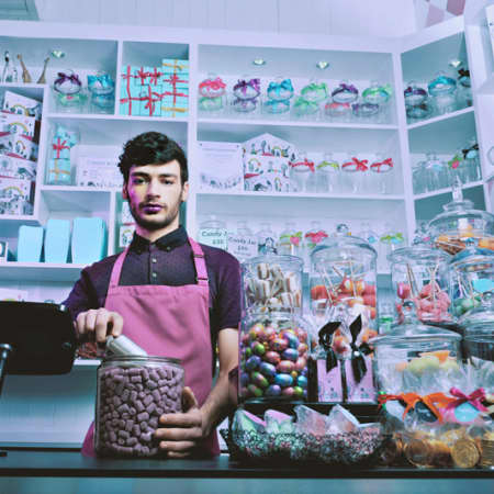 Male model in apron behind sweets counter.