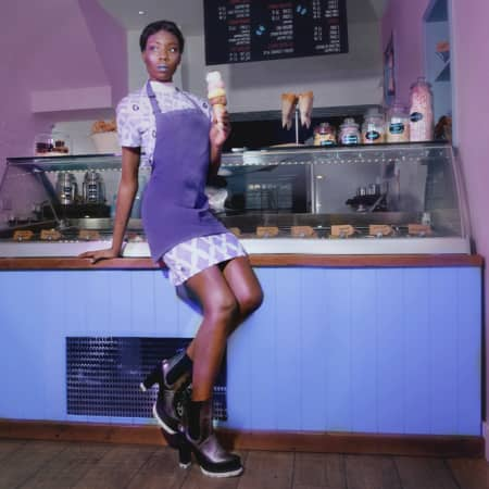 Model in purple apron lounging on a shop counter.
