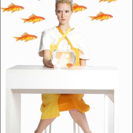 Model behind desk with floating goldfish.