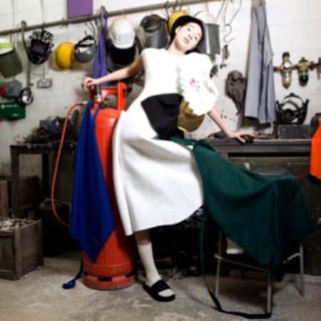 Model lounging in workshop, with aprons draped