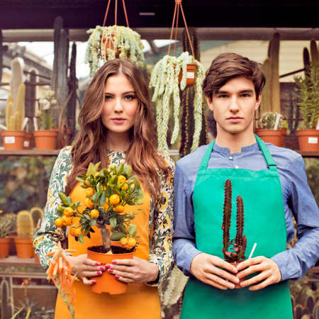 Girl and boy with flowers, wearing aprons.