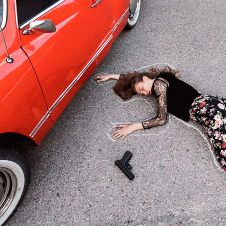 Model lying on the ground in floral trousers, next to a red vintage car