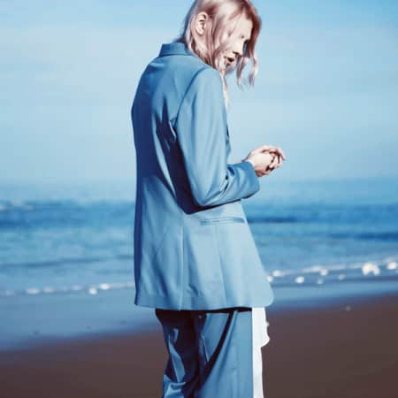 Model in blue suit against blue sky and sea
