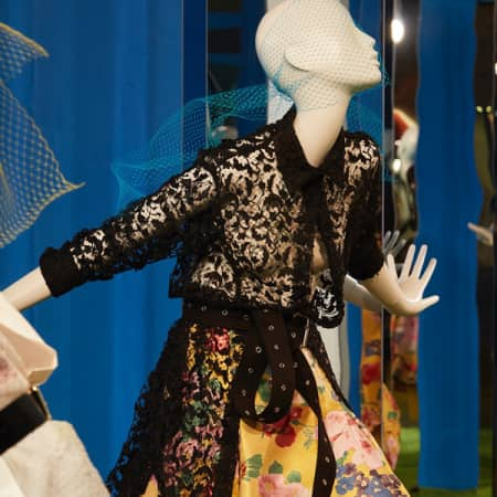 Mannequin in black lace cardigan and dress in front of blue background
