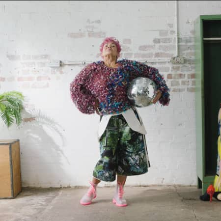 Older lady in a room in bright outfit next to a plant and wardrobe with dress hanging on it