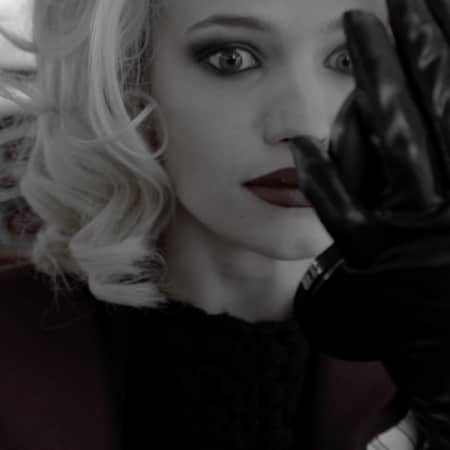Model with blong curls and black gloves