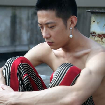 Male model sitting with his arms around his legs and pearl in his ear