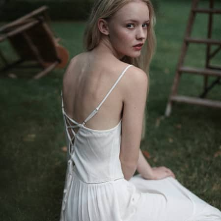 Model in white slip dress with back turned to camera.