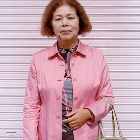 Lady in pink jacket in front of pink wall