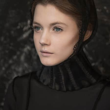 Model in black victorian cape and bonnet