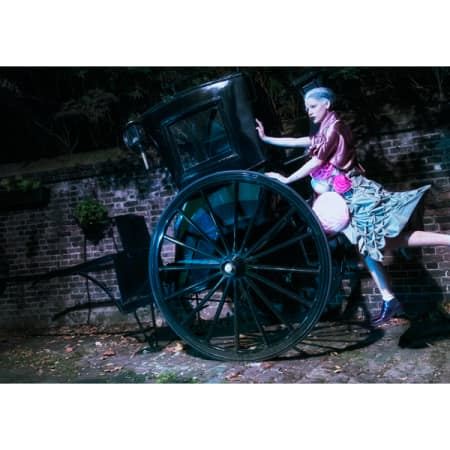 Model posing on an old fashioned cart