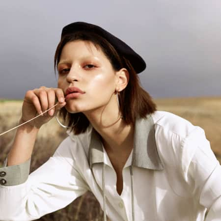 Girl in beret in a field with bleached eyebrows