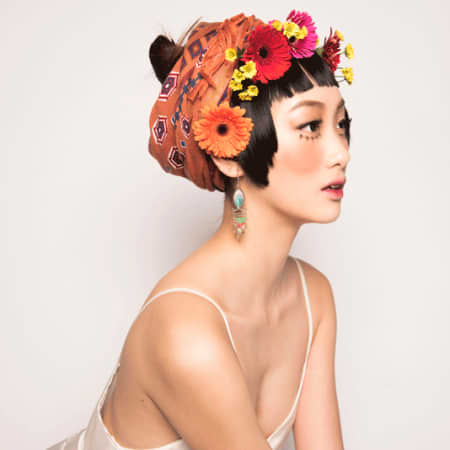 Model in slip and headscarf with flowers and exaggerated eyelashes on her cheeks