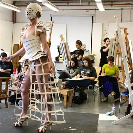 Students drawing a model in white caged skirt, corset and headpiece.