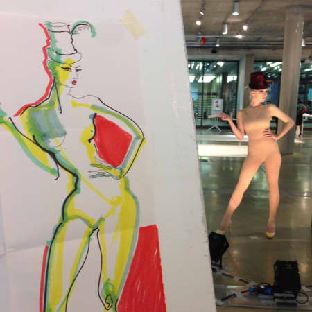 Colourful sketch of a model, with actual model in background.