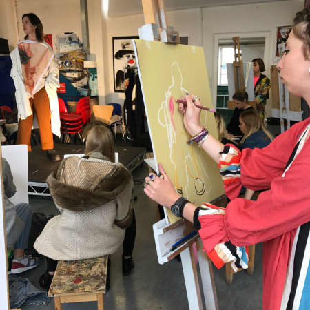 Student with easel, drawing in white on brown.