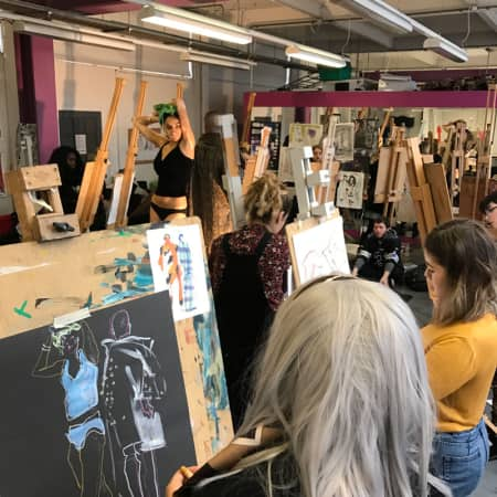 Students with easels in drawing studio