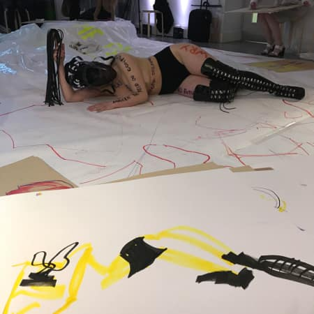 Model in black leather boots with writing on her body, lying on student sketches