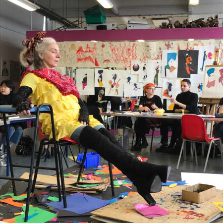 Model in yellow top, sitting amongst chairs and sketches in drawing class.