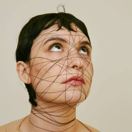 Model with short dark hair and spider's web design over her face.