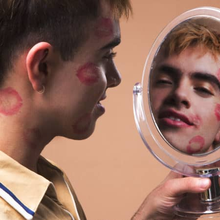 Male model looking in the mirror, with kiss marks on his cheeks