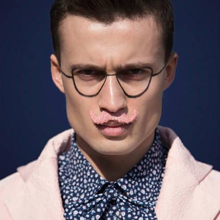 Male model with pink moustache and pink jacket and slick back hair.