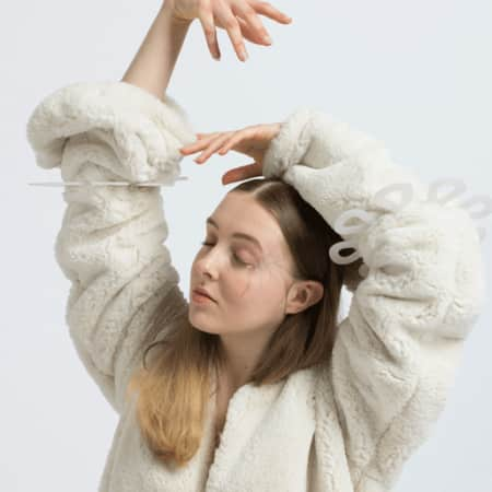 Model with hands above head, wearing cream shearling.