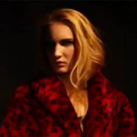 A hazy image of a model in a red leopard print coat