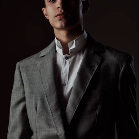 Male model in grey suit and collarless shirt.
