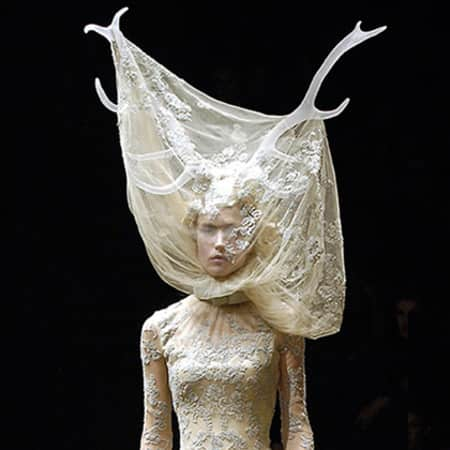 A model on the Alexander McQueen catwalk wears white antlers and a lace dress.