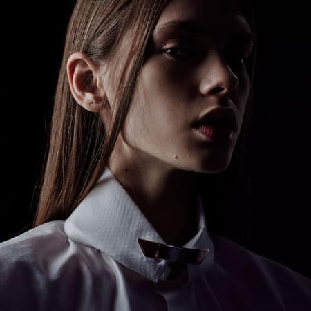 Close up of model with shirt collar and dark background