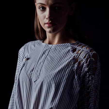 Female model wearing stripe shirt with lattice shoulders