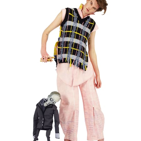 A male model in pink clothes with a knitted vest holding a ghoulish marionette.