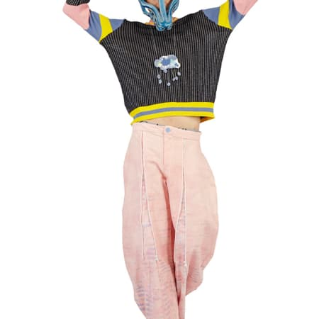 A model in pink trousers and a ribbed jumper, wearing a dog's head mask.