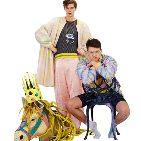 Two male models in pastel clothing with a puppet horse's head.